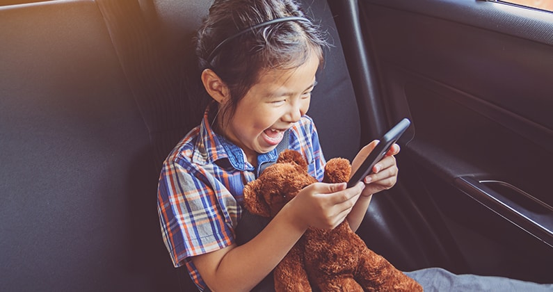 Child in a car playing with a mobile device